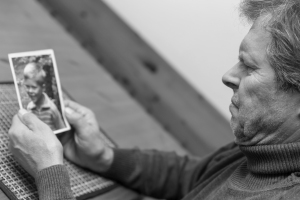 Black and White Portrait of Elderly Man Looking at Portrait of Young Boy