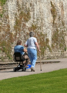 Woman in Wheelchair, Woman with Cane Walking